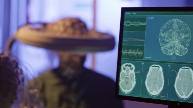 vídeos de stock, filmes e b-roll de homem usando fone de ouvido brainwave escaneando. - equipamento médico