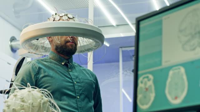 vídeos de stock e filmes b-roll de man wearing brainwave scanning headset. - cérebro humano