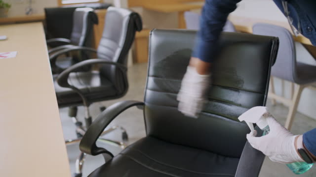 man wearing face mask and plastic glove using aerosol spray alcohol for cleaning office chair during covid-19 virus - bar lokal gastronomiczny filmów i materiałów b-roll