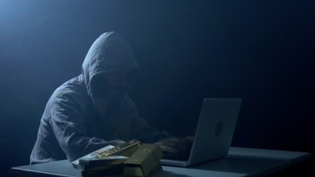Man Wearing Hooded Shirt And Using Laptop In Dark To Hack video