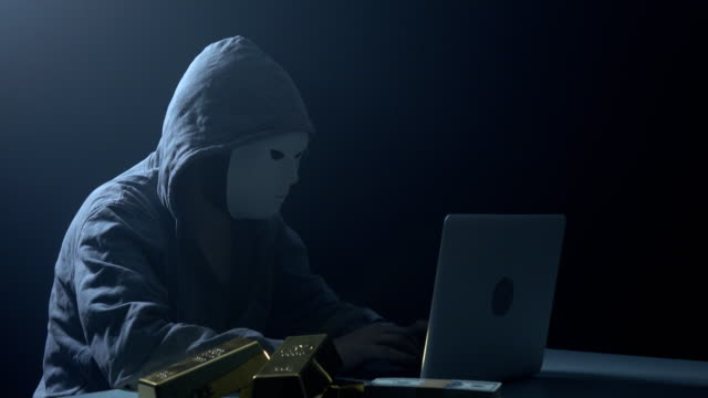 man wearing hooded shirt and using laptop in dark to hack - anonymous hackers stock videos and b-roll footage