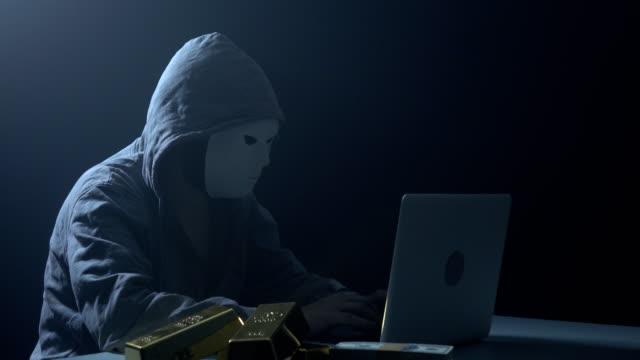 stockvideo's en b-roll-footage met man dragen hooded shirt en met behulp van laptop in donker voor kappen - onherkenbaar persoon