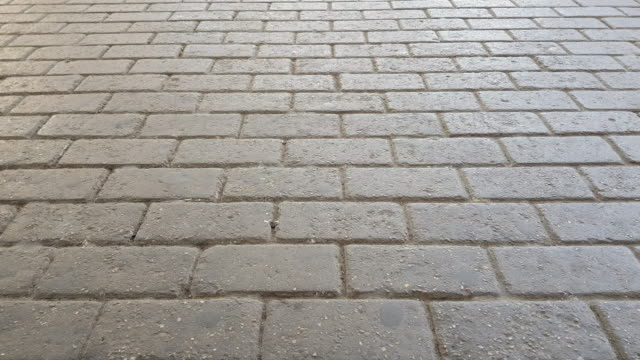 Man wearing jeans and leather shoes walking on cobblestone pavement video