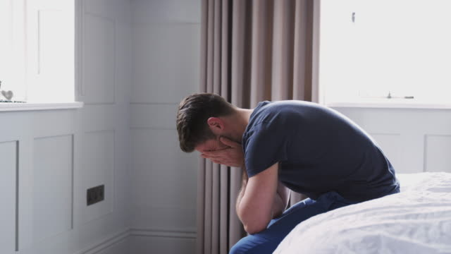 mann trägt pyjamas leiden mit depression sitzen auf dem bett zu hause - depression stock-videos und b-roll-filmmaterial
