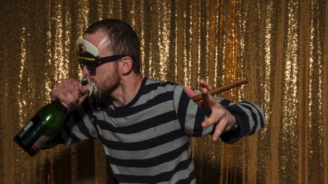 A man wearing props and taking party photos in a photo booth