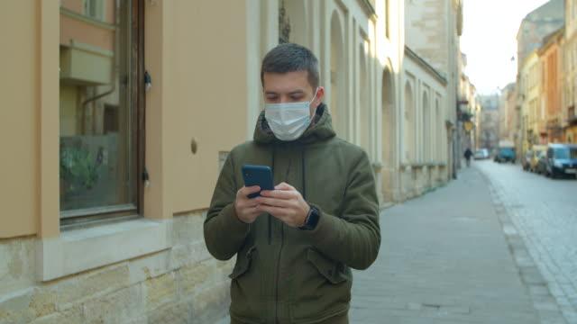 mann trägt schutzmaske verwenden sie telefon. covid-19 coronavirus-infektion. porträt eines kaukasischen mannes in einer medizinischen gesichtsmaske. pandemie covid-19 coronavirus-schutz - smartphone mit corona app stock-videos und b-roll-filmmaterial