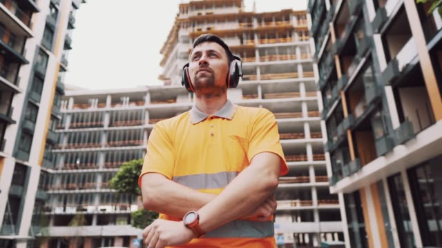 Man wearing safety equipment hearing protection. Worker wearing noise cancelling ear defenders or ear muffs. Construction builder puts on protect ears with headphones. Taking care safety during work