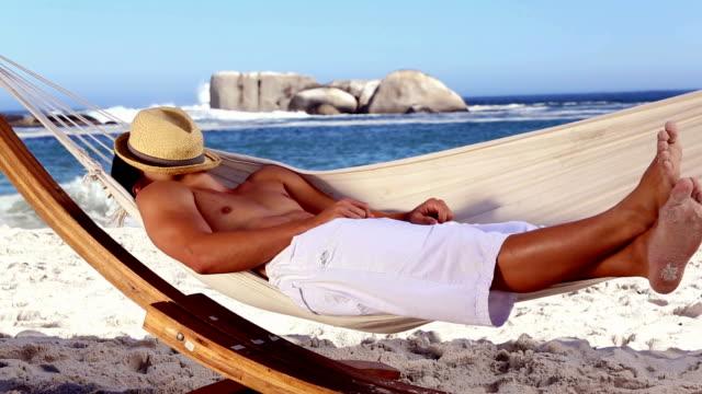 mann mit strohhut entspannen in der hängematte - strohhut stock-videos und b-roll-filmmaterial