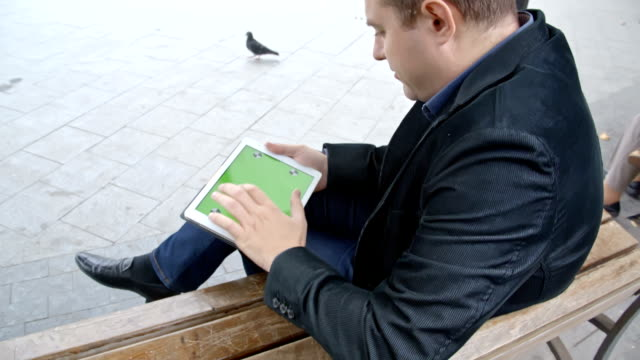 Man Wearing Suit Working With Tablet On A Bench, Greenscreen video