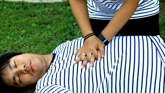 RESCUE CPR TRAINING TO SAFE LIFE Man wearing t-shirt stripes lay down and women with white Long-sleeved shirt trains CPR on the grass background, Concept In the process of resuscitation (first aid) video