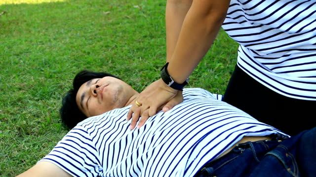 RESCUE CPR TRAINING TO SAFE LIFE Man wearing t-shirt stripes lay down and women with white   Long-sleeved shirt trains CPR on the grass background, Concept In the process of   resuscitation (first aid video