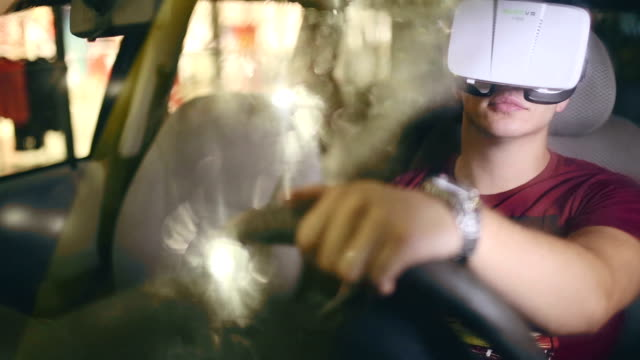 Man wearing virtual reality goggles  and playing car racing game in his car while is raining video