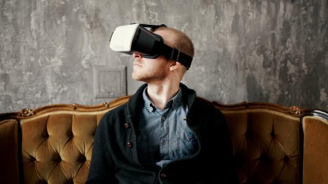 Man wearing virtual reality goggles. Studio shot, gray backgroun video