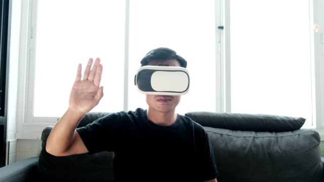 Man wearing VR goggles in living room at home