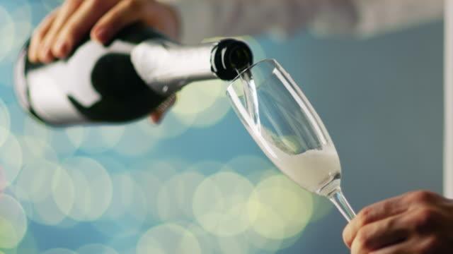 vidéos et rushes de homme portant chemise blanche versant de champagne dans le verre de champagne. arrière-plan est bleu avec floue lights shining. - flûte à champagne