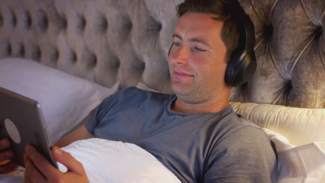 Man Wearing Wireless Headphones Lying In Bed Watching Digital Tablet Before Going To Sleep