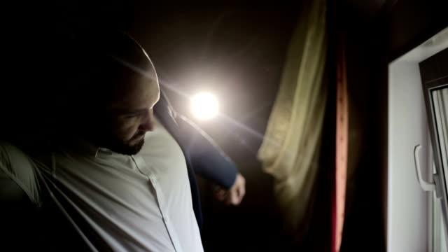 Man wears a jacket in early morning in dark room video