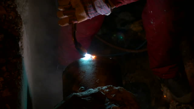 A man welding a central heating system pipe at night in an urgent intervention video