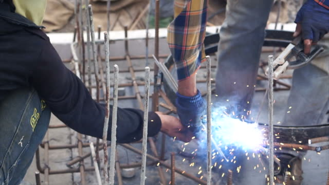 Man welding metal on site at work construction site video