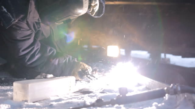 Man Welds Machine Components in Arctic Welder in safety helmet and protective clothing welds machine elements in snow above Arctic circle at night metal worker stock videos & royalty-free footage