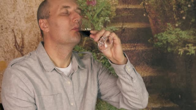 Man winemaker drinking red wine from glass. Man sommelier tasting wine close up. Show thumbs up ok sign gesture. video