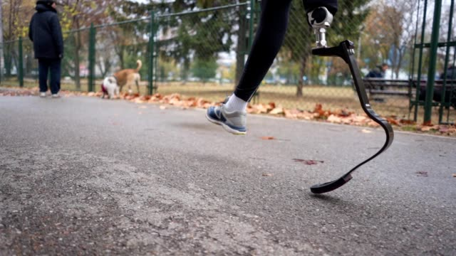 Man with a artificial leg jogging outdoors in a park Young and athletic man with a artificial leg, exercising outdoors, living a healthy lifestyle recovering. artificial limb stock videos & royalty-free footage