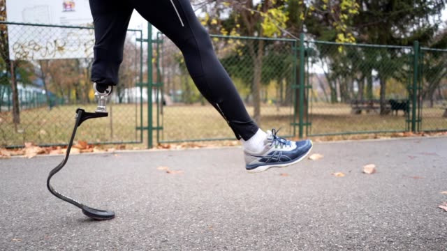 Man with a artificial leg warming up before running Young and athletic man with a artificial leg, exercising outdoors, living a healthy lifestyle recovering. artificial limb stock videos & royalty-free footage