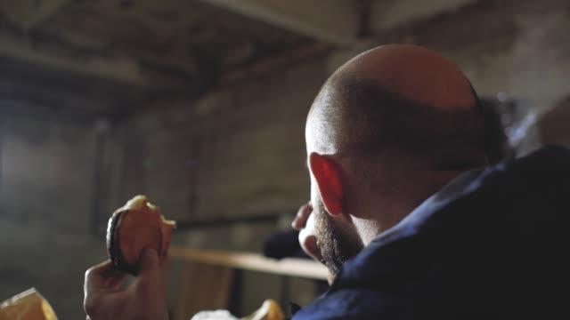 stockvideo's en b-roll-footage met man met een kale kop drinkt thee uit een wegwerp beker en eet een broodje - camelia white