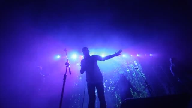 en man med en band som sjunger på scenen. en snabb låt. lila ljus. röker - sångare artist bildbanksvideor och videomaterial från bakom kulisserna