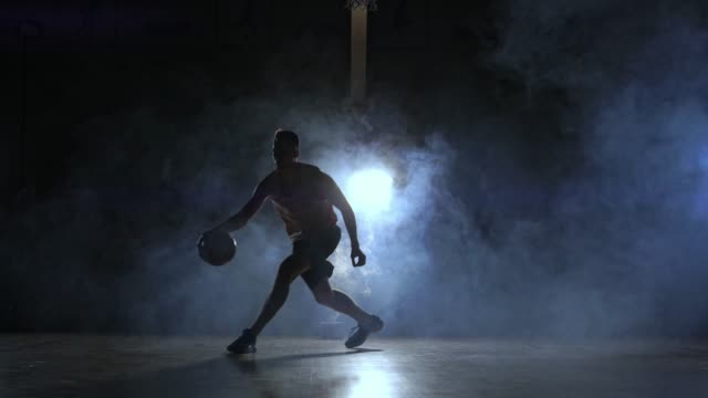 a man with a basketball on a dark basketball court against the backdrop of a basketball ring in the smoke shows dribbling skills illuminated by three lanterns in backlight - iluminacja filmów i materiałów b-roll