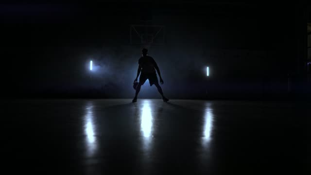 a man with a basketball on a dark basketball court against the backdrop of a basketball ring in the smoke shows dribbling skills illuminated by three lanterns in backlight - basketball stock videos and b-roll footage