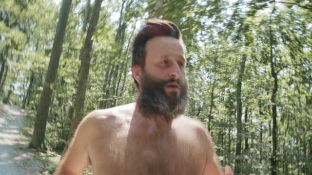 ts mann mit bart und keine shirt laufen durch den wald - nackter oberkörper stock-videos und b-roll-filmmaterial