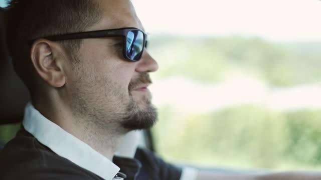 vídeos de stock, filmes e b-roll de um homem com uma barba e óculos de sol dirige um carro. - moda urbana