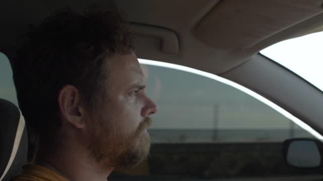 man with a beard is driving a car with an attentive expression. guy drives a car on the background of the sea. 4k. 4k video. slow motion. 23.98 fps