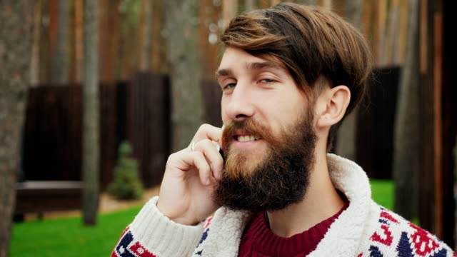 A man with a beard speaks on the phone video