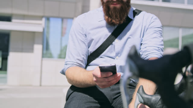 DS Man with a beard using a smartphone in front of the office building video