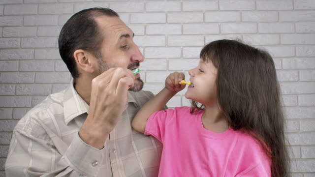 a man with a child brushing teeth. morning treatments. - bagno domestico video stock e b–roll