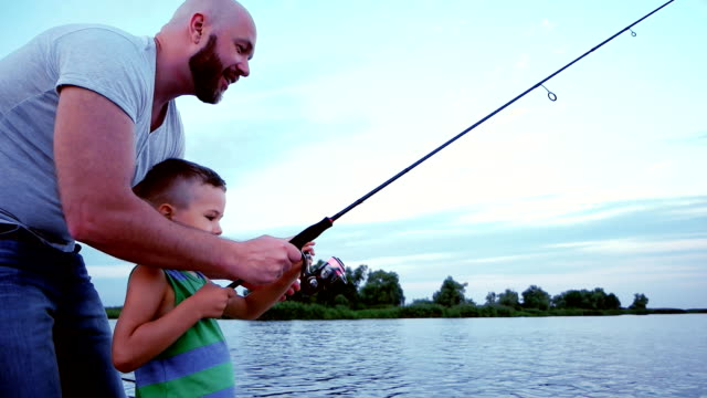 man with a child on a fishing trip, father and son catches a fish with spinning rods, outdoor recreation on the lake, fisherman sitting in a boat, throw fishing rod with bait video
