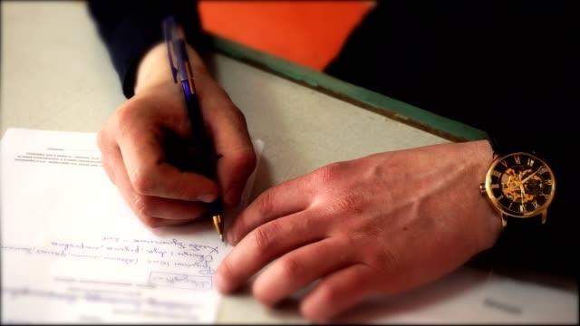 vídeos de stock, filmes e b-roll de um homem com um relógio na mão, escrevendo uma carta. close-up de mãos masculinas. - assistente jurídico