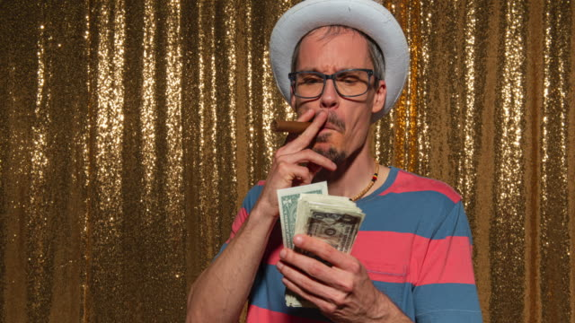 Man with a funny hat and a cigar counting money while posing in the photo booth