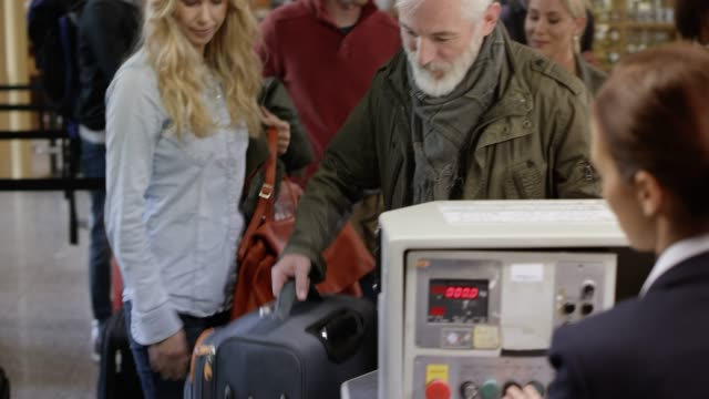 Man with a grey beard placing his bag on the conveyor belt at the check in desk video