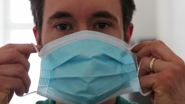 man with a medical mask in self quarantine at home - nakładać filmów i materiałów b-roll