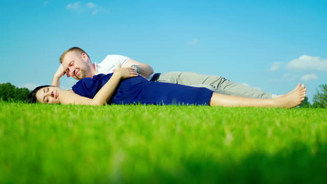 A man with a pregnant wife is lying on the green grass. Against the background of the blue sky video