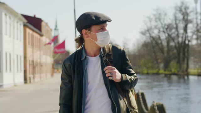 Man med en skyddande ansiktsmask som går ensam genom staden video