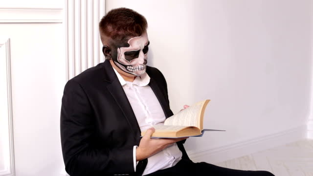 A man with a terrible make-up in the form of a skull is holding a book.Halloween