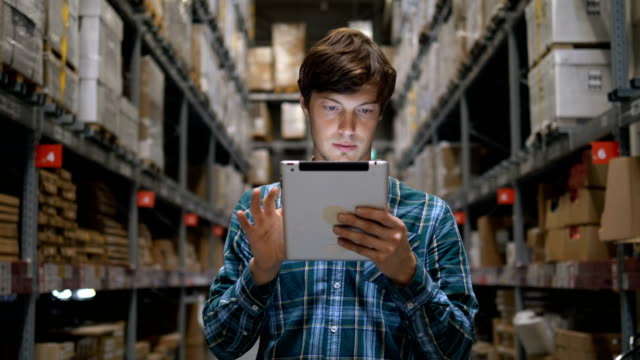 A man with an electronic tablet in his hands stands in a warehouse with products, the Manager of the logistics service - vídeo