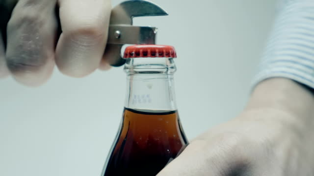 A man with an opener opens a metal cork in a glass bottle with a cooling drink