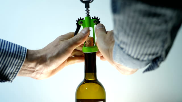 A man with an opener opens a wooden cork from a bottle of wine A man with an opener opens a wooden cork from a bottle of wine (an alcoholic drink). Closeup cork stopper stock videos & royalty-free footage