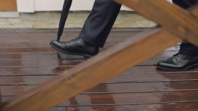 vídeos y material grabado en eventos de stock de un hombre con un paraguas va en el tiempo de lluvia en un suelo mojado. cierre para arriba - novio relación humana