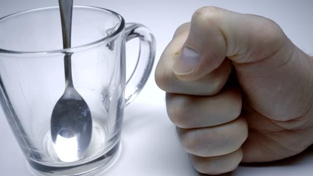 vídeos de stock, filmes e b-roll de um homem com raiva socado pelo punho na mesa branca em que está um copo de vidro - braço humano